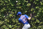 New York Mets right fielder Mike Baxter crashes into the ivy-covered wall trying to catch a hit by Chicago Cubs pitcher Scott Feldman. Photo / AP