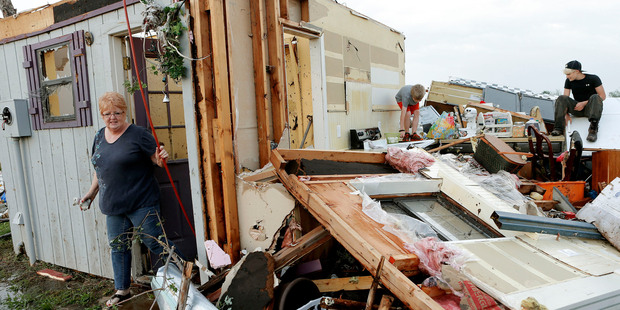 Marlena Hodson and her grandsons Campbell and Dillon Miller sort through what's left of her Oklahoma trailer home. Photo / AP
