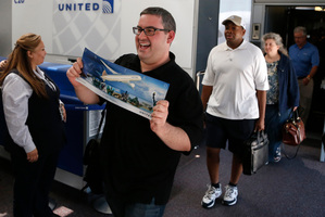 A United passenger shows off a commemorative poster. Photo / AP