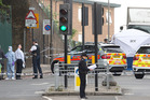 Police and forensic officers near the scene of an attack which has left one man confirmed dead and two people wounded near Woolwich barracks in London Wednesday, May, 22, 2013. Scotland Yard said offi