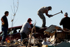 James Pitts uses a sledge hammer to try to force open a friend's trunk in a tornado-ravaged car as residents sort through their tornado-ravaged homes. Photo / AP