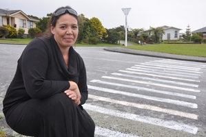 Stirling Drive resident Line Low next to the 'pedestrian crossing' that popped up at Arnott Heights, Greymouth, yesterday. It has since been washed off by contractors. Photo / Greymouth Star