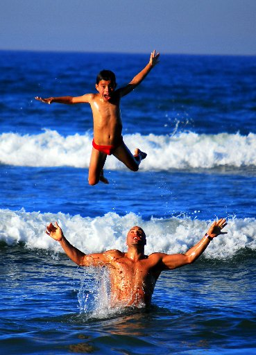 """Photo supplied by Helen Hamilton. """"This is a photo of my son and law and grandson Tai, at Papamoa beach. They have a raft of acrobatic tricks both in and out of the water."""""""