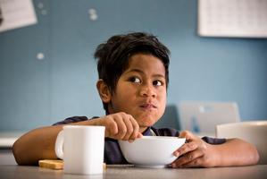 Filo Kaio, 7, enjoys his breakfast before starting his morning at Randwick Park School in Manurewa. Photo / Greg Bowker
