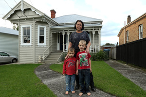 Laurene Dearlove with sons Mason, 2 and Riley, 4, in front of their home which has been moved from Western Springs to Morningside. Photo / Getty Images