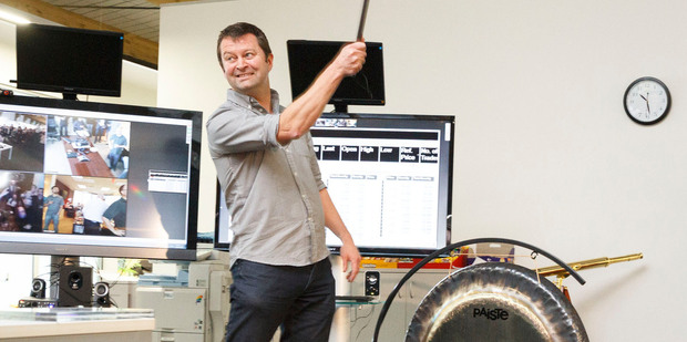 SLI Systems co-founder Shaun Ryan strikes a gong as SLI debuts on the NZX last week. Photo / Supplied