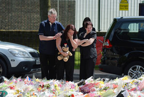 Lyn Rigby, mother of Drummer Lee Rigby, holding a teddy bear, joins other family members outside Woolwich Barracks. Photo  / AP