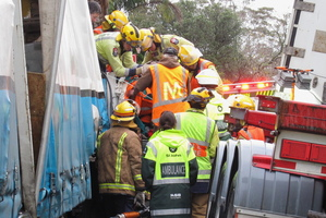 Firefighters and St John staff attend to one of the drivers involved in the Kerikeri crash yesterday. Photo / APN