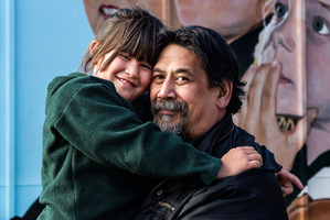 Andrew Smith with his daughter Serenity in front of a mural of her at the school yesterday. Photo / Martin Hunter