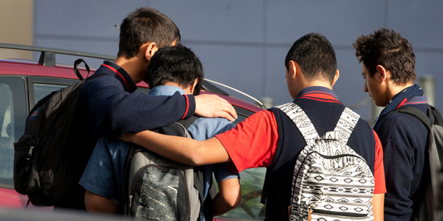 Kelston Boys High School students console each other as they try to come to terms with the death of Stephen Dudley after a rugby training session. Photo / Natalie Slade