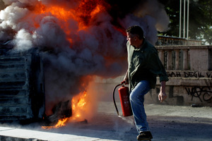 A protester holding a fire extinguisher moves away from a burning car during a protest at Taksim Square in Istanbul. Photo / AP