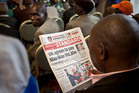 A Kenyan man reads a copy of Kenya's The Standard newspaper as Mau-Mau veterans await a press conference about an announcement regarding their legal case for compensation. Photo / AP