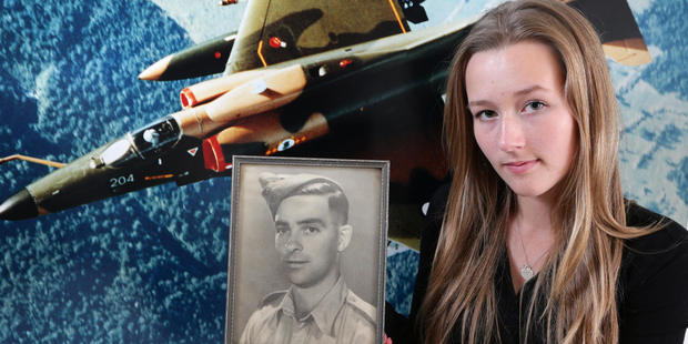 Diana is holding a photo of her soldier grandfather Dougall Drysdale in front of a picture of her father Ross flying a Skyhawk while in the RNZAF. Photo / Courier Mail