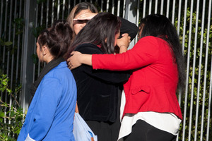 Two women console each other outside Kelston Boys High School as parents and students try to come to terms with the death of a student. Photo / Natalie Slade