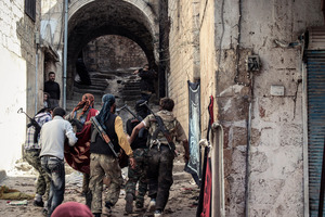 A group of Free Syrian Army fighters carry a wounded comrade in the town of Harem, Syria. Photo / AP
