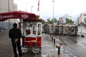 A bagel vendor stands behind a destroyed mini bus the Taksim Square in Istanbul. Photo / AP