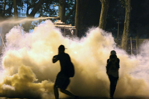Police use water cannon as protesters run to avoid tear gas. Photo / AP