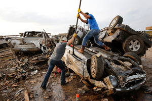 Two men attempt to pry open a door on this car to check for victims in a business parking lot west of I-35 south of 4th Street in Moore. Photo / AP