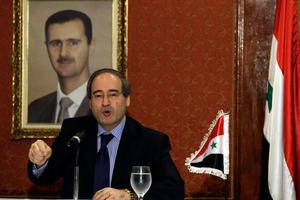 Backdropped by a framed picture of Syrian President Bashar al-Assad, is Syria's Deputy Foreign Minister Faisal al-Mokdad. Photo / AP