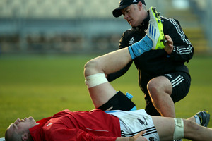 Physiotherapist Peter Gallagher attends to Brodie Retallick of the All Blacks during a New Zealand All Blacks training session at AMI Stadium. Photo / Getty Images.