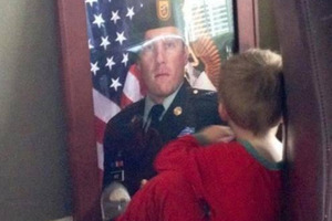 Traci Wise took a picture of her son Luke Wise next to a photograph of his father SFC Benjamin Wise who was killed in action in Afghanistan.
