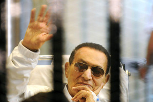 Hosni Mubarak waves to his supporters from behind bars. Photo /AP