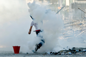 A protester throws back a tear gas canister towards riot police during clashes at the Taksim Square in Istanbul. Photo / AP