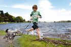 Nine-year-old Tom Farrar with his dog 'Billy', a Miniature Schnauzer, playing in the puddles on the edge of Hamilton Lake. Photo / NZH