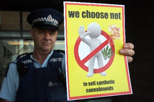 Constable Dean Fawcett and the poster 'We choose not to sell synthetic cannabinoids'.