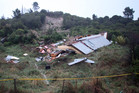 Only a wall and the roof remained intact after the landslide hit the rear of the house in Tasman and pushed it off its piles. Photo / Tim Cuff
