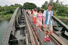 Tourists cross the bridge on the River Kwai in Kanchanaburi. Below: Peter Feeney and his children visit the Death Railway.