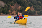 Elisabeth Easther and son take to the water; kayaks on the beach at Tawhitokino campground. Photo / Nic Mead