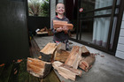 Benjamin Foster, 6, with firewood donated to his family after all their wood was stolen. Photo / Joel Ford
