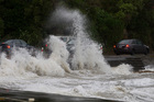 Motorists braving the conditions on Marine Drive, Eastbourne, shortly after the tide peaked today. Photo / Mark Mitchell