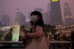 A woman braves the haze as the Singapore CBD is covered with smog which is hitting record-breaking levels. Photo / AP