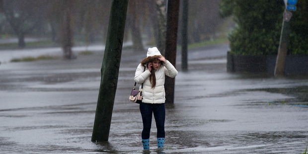 Loading A young woman walks along a flooded Avonside Drive after the Avon River broke its banks earlier this week. Photo / NZ Herald