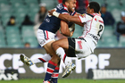 Sam Moa of the Roosters is tackled by Glen Fisiiahi. Photo / Getty Images