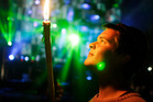 Festival goer Alan Linn, 21 of Leeds, looks at his candle in the Block 9 area of the Glastonbury Music Festival site. Photo / AP