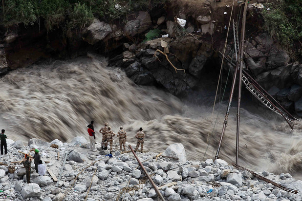 Water gushes down a river as Indian paramilitary soldiers and volunteers stand near a makeshift bridge after it was damaged hampering to evacuate the stranded pilgrims in Govindghat, India. Photo / AP