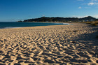 Whangamata's stretch of golden sand is a popular spot for summertime sun-seekers. Photo / Lion Hijmans