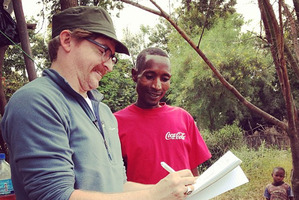 Rhys Darby met entrepreneur Lucas in Tanzania, to whom he is giving a micro loan to help his business self-sufficiency as part of a World Vision trip.