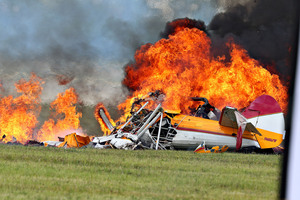 Flames erupt from the bi-plane in which the stunt pilot and Jane Wicker, seen below on the wing moments before the crash in Ohio, were killed. Photo / AP