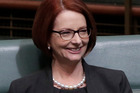 Former Australian Prime Minister Julia Gillard smiles after arriving in chambers at parliament today. Photo / AP