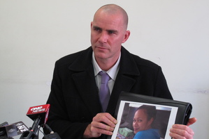 Detective Senior Sergeant Rhys Johnston with a photo of missing Northland woman Barbara Moka.
