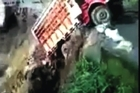 Dramatic footage as India's monsoon floods wash away vehicles and homes with one truck falling into a gorge, officials now fear more than 1,000 dead.
