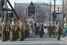 The ruins of Christchurch Cathedral form the backdrop as New Zealand Defence Force personnel march into Worcester Boulevard for a ceremony marking the end of the Red Zone. Photo / SNPA