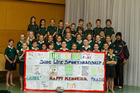 Hauraki School rugby coach Peter Cullen with his team and the behaviour-changing banner they designed. Photo / Michael Craig