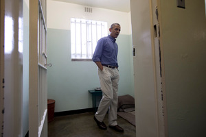 U.S. President Barack Obama looks out from Section B, prison cell No. 5, on Robben Island, South Africa. The cell housed Nelson Mandela for most of his 27 years in jail. Photo / AP