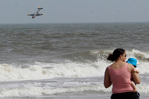 A woman and her child are seemingly unaware as the plane, with two off-duty policemen on board, crashes into the Atlantic Ocean. Photo / AP