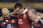 British and Irish Lions' captain Sam Warburton, center, is helped off the field by team trainers while playing Australia in their rugby union test match. Photo / AP